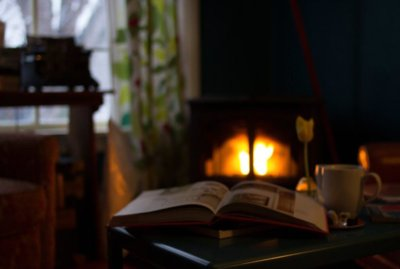 Open book open on table next to coffee cup in front of fireplace